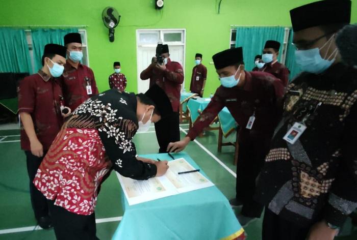 Kepala Kankemenag Kab. Cilacap, Imam Tobroni menandatangani berita acara pengukuhan Tim Zona Integritas MAN 2 Cilacap
