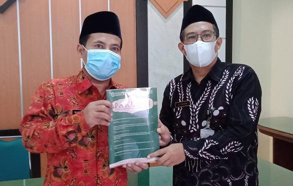 Kepala Kankemenag Kab. Cilacap menerima jurnal Pakerti dari ketua DPD PGMI Kabupaten Cilacap